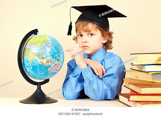 Little boy in academic hat showing on the globe among the old books