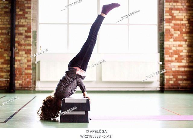 Full length side view of female dancer doing handstand on steps
