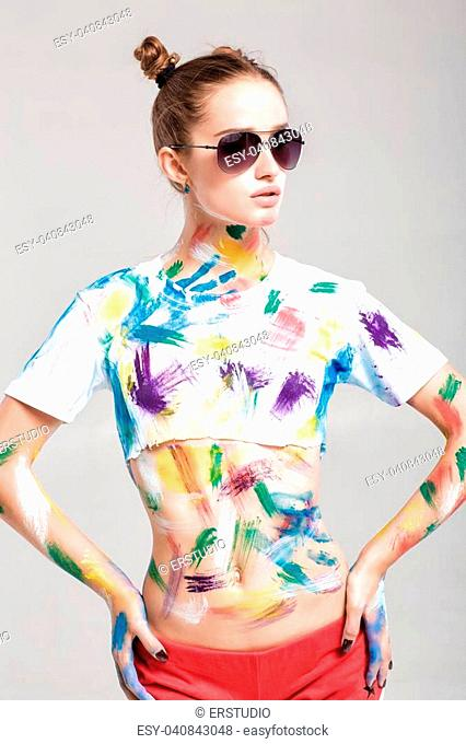 beautiful young woman in sunglasses is dirty in multicolored paint