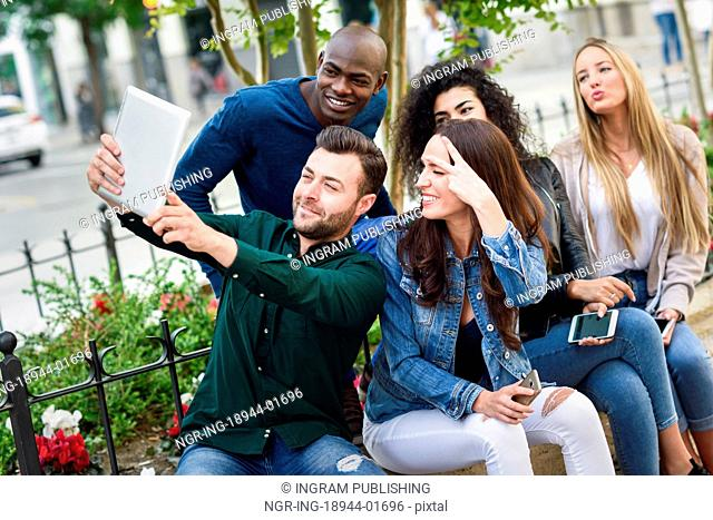 Multi-ethnic group of young people taking selfie photograph together outdoors. Beautiful funny women and men wearing casual clothes in urban background