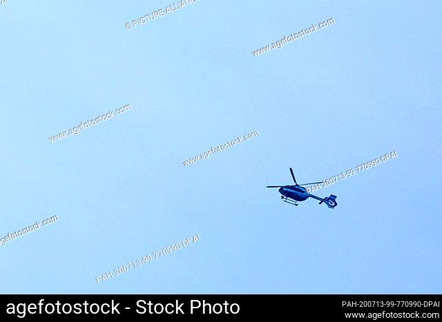 13 July 2020, Baden-Wuerttemberg, Oppenau: A police helicopter flies over the forest near the community of Oppenau. A large police contingent has been searching...