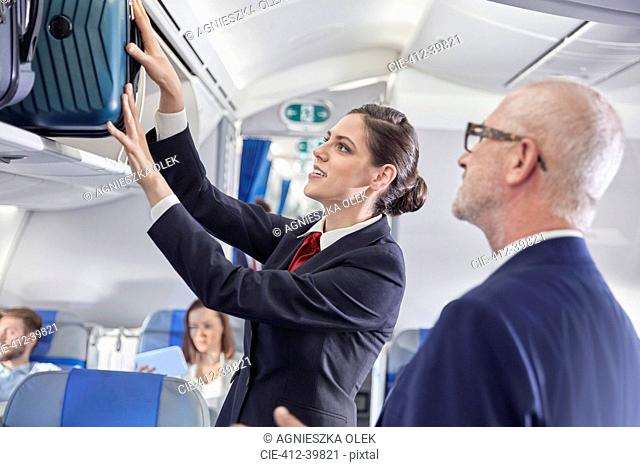 Flight attendant helping businessman place luggage in overhead compartment on airplane