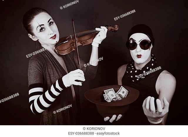 Portrait of Two mimes playing a violin for the money