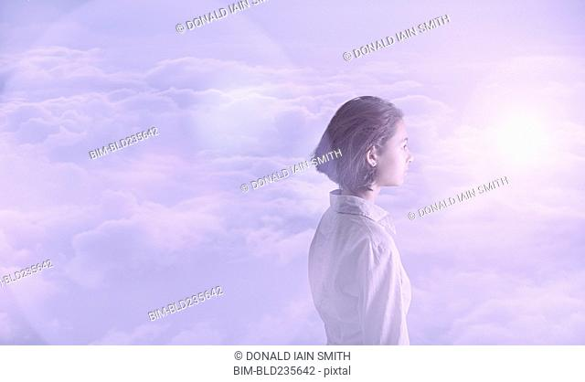 Pensive Mixed Race girl in clouds