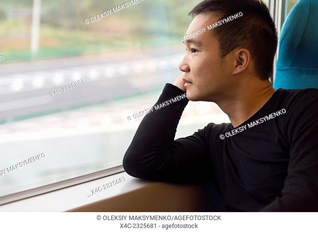 Person looking out of a window of a high-speed train in Shanghai, China