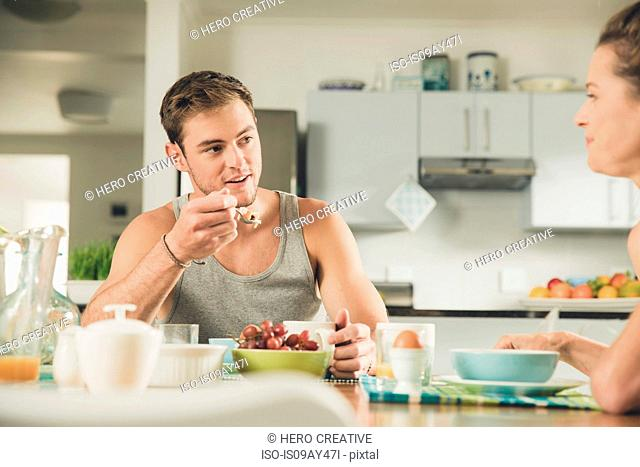 Young couple eating fruit breakfast at kitchen table