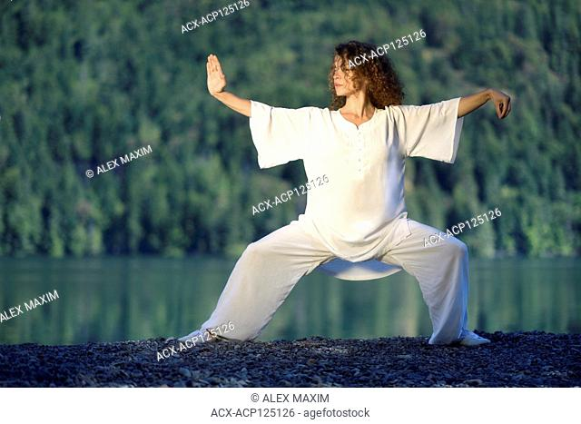 Young woman in white silk uniform practicing a Tai Chi, Taiji, Ban Ma Bu stance in the morning sunrise by the mountain lake in the nature