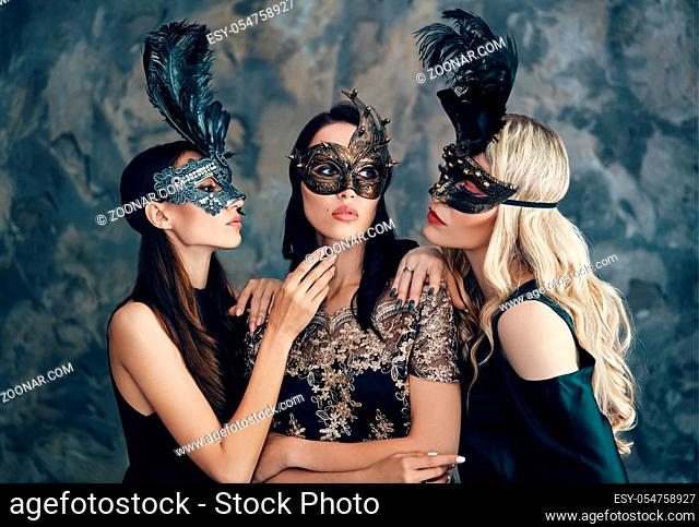Beautiful young women in mysterious venetian mask. Fashion photo concept