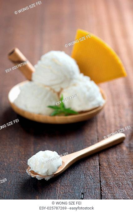 Scoop vanilla ice cream with waffle on wood background. Focus on front spoon