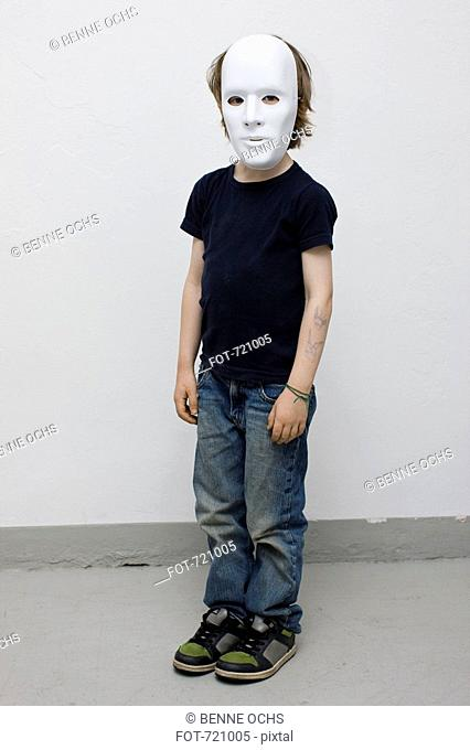 A young boy wearing a mask