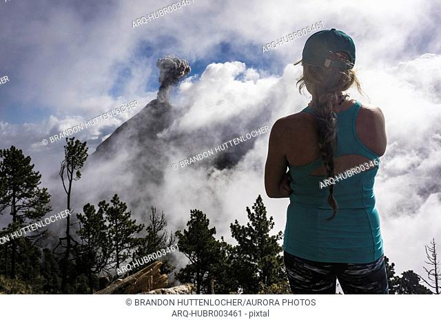 Rear view shot of young female hiker looking at view of Fuego Volcano, Guatemala