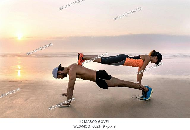 Athletes couple training on the beach at sunset, pushups