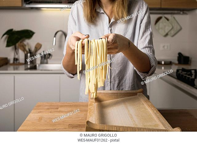 Woman preparing homemade pasta, holding row noodles, pasta harp