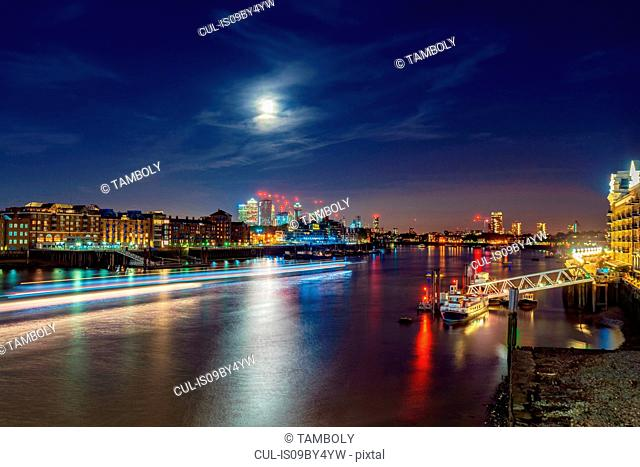Night view of Thames river and financial district, Isle of dogs in background, City of London, UK
