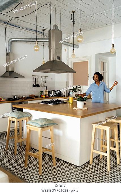 Woman having a healthy breakfast in her kitchen, listening music