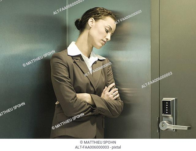 Woman leaning head against wall next to door