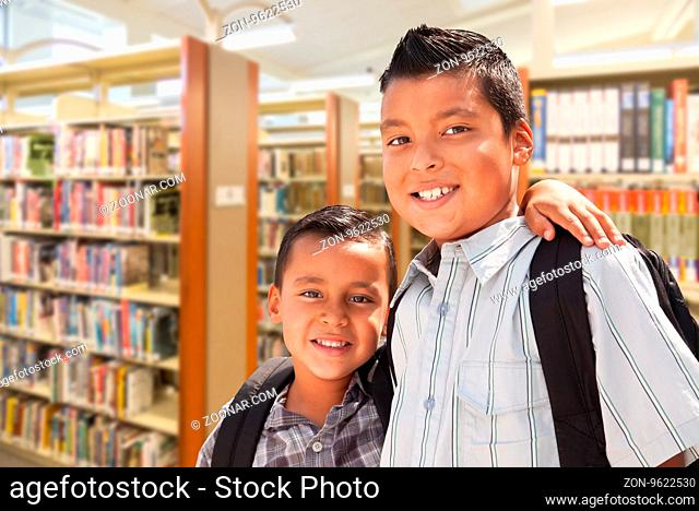 Happy Young Hispanic Student Brothers In Library