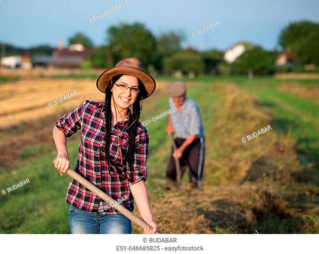 Young pretty farmer girl helping grandfather with work in field