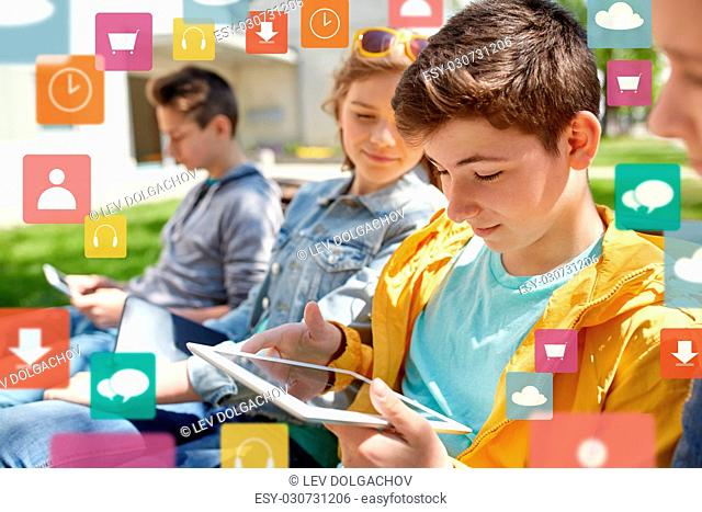 technology, internet and people concept - group of happy teenage friends or high school students with tablet pc computer outdoors over virtual icons