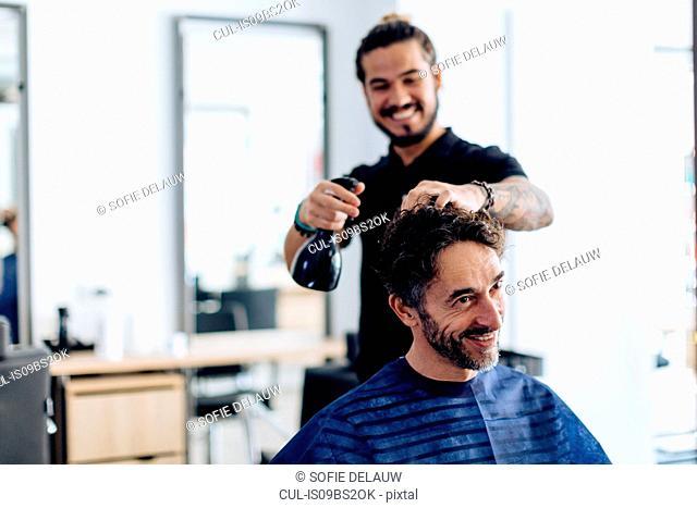 Male hairstylist spraying male customer's hair in hair salon