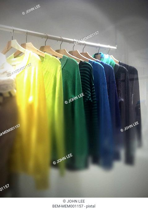 Colorful sweaters hanging on rack