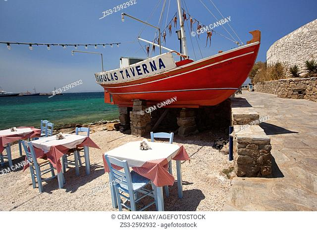 Outdoor restaurant-taverna with the hanging octopuses at the background by the seaside in town, Mykonos, Cyclades Islands, Greek Islands, Greece, Europe