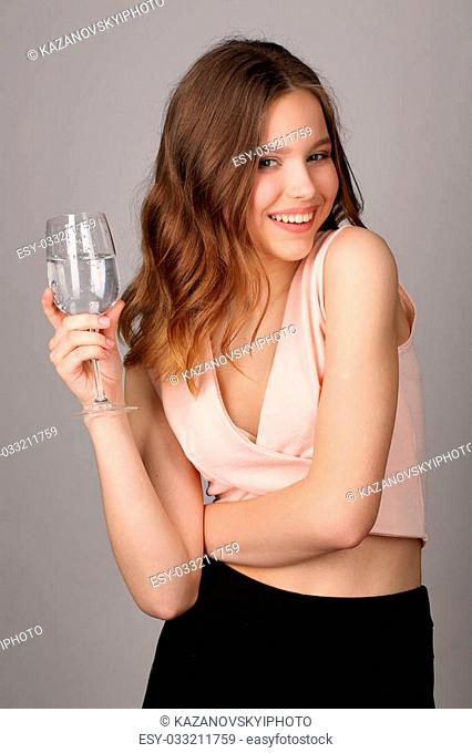 Model posing with wine glass of water, high fashion look, healthy lifestyle, beautiful girl, smiling girl, isolated, perfect make-up, big lips, model in studio