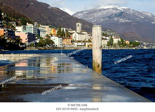 Viillage with a lake and snow-capped mountains