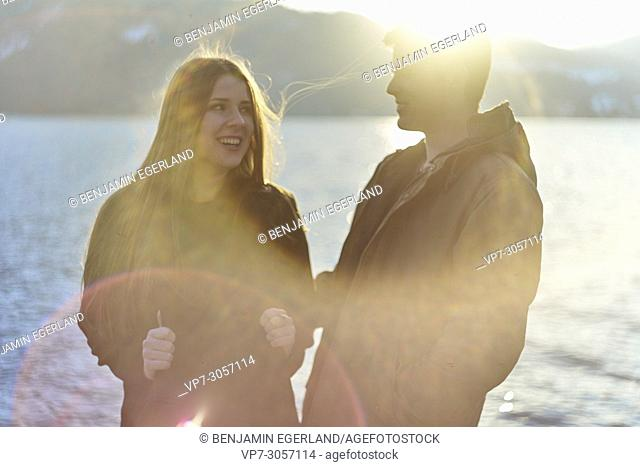 Tegernsee, Germany, laughing couple next to lake, sunny weather, winter clothes