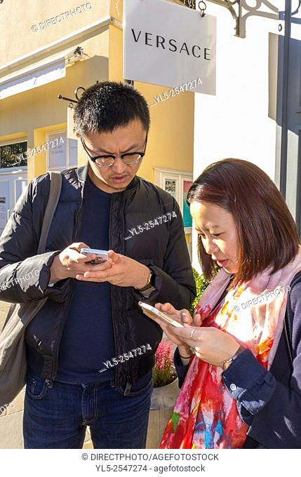 Paris, France, Chinese Couple Tourists Shopping in Luxury Stores in La Vallee Village, Discount Shops, using Iphone on Street M.R