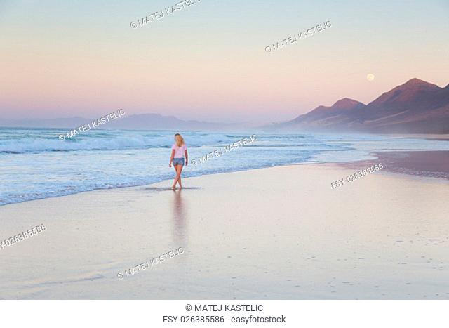 Woman walking on sandy beach in sunset. Waves sweeping away her traces in sand. Beach, travel, concept. Copy space