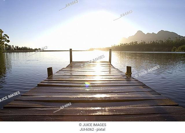 South Africa, wooden jetty on tranquil lake at sunset lens flare