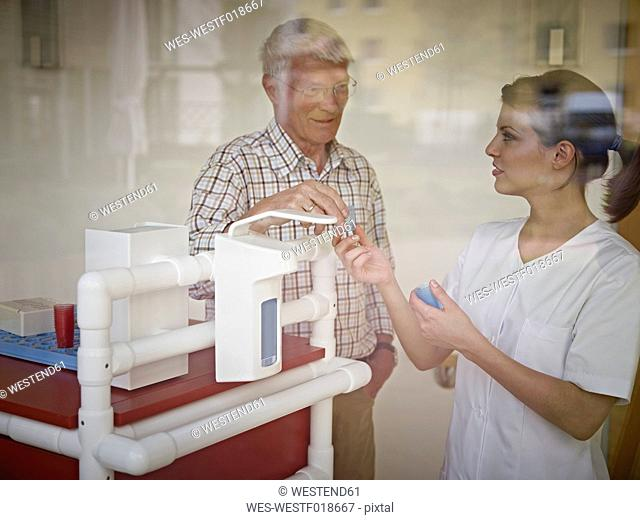 Germany, Cologne, Caretaker giving medicine to senior man in nursing home