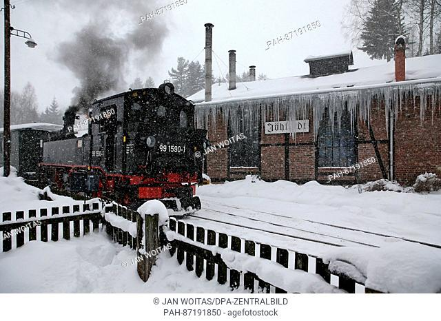 A steam train on the Joehstadt narrow-gauge railway traverses a snowy landscape in the state of Saxony in Germany, 13 January 2017