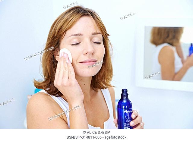 Woman applying lavender floral water on her face