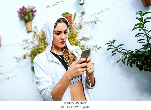Young woman wearing headphones and wrtiting text message