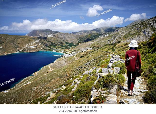 Woman walking on the historical hiking trail going from the Panagia Hozoviotissa monastery to Aegiali village, reaching Potamos