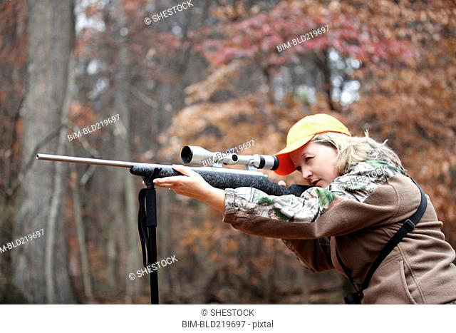Hunter in camouflage aiming rifle in forest