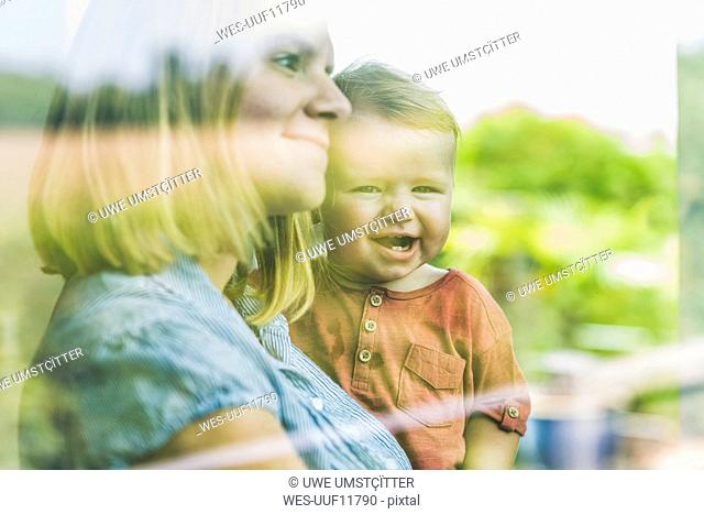 Mother looking out of window, with son on her arm