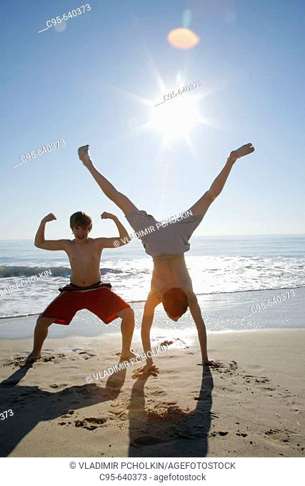 Virginia Beach, Virginia, USA, 2 boys playing on the beach, 13 years old