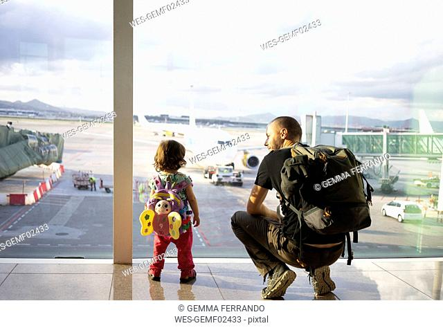 Father and daughter with backpacks at the airport looking at the planes