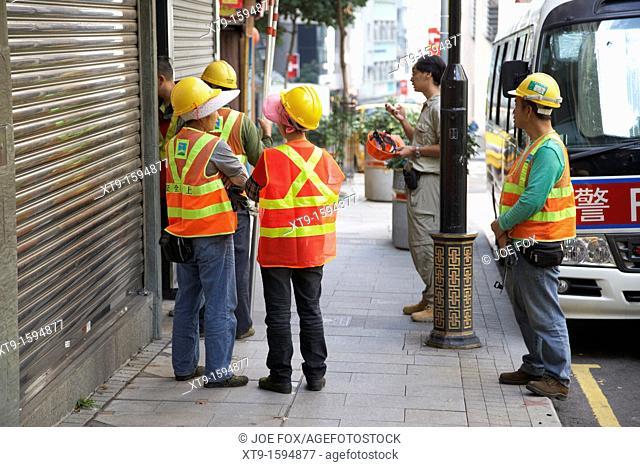 chinese construction building workers wearing high vis vests enter a building hong kong hksar china