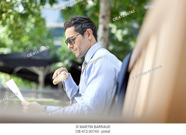 Corporate businessman eating lunch and reading paperwork on park bench
