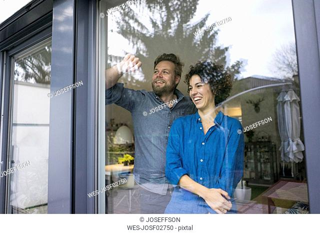 Happy couple behind window at home looking out