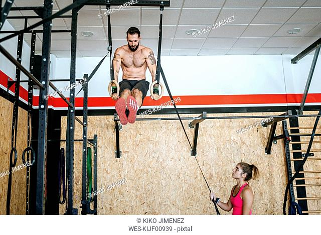 Man doing exercises on rings in gym with woman assisting