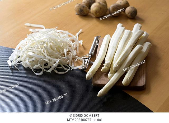 Peeled asparagus with peeler and potatoes on table, Freiburg im breisgau, Baden-württemberg, Germany