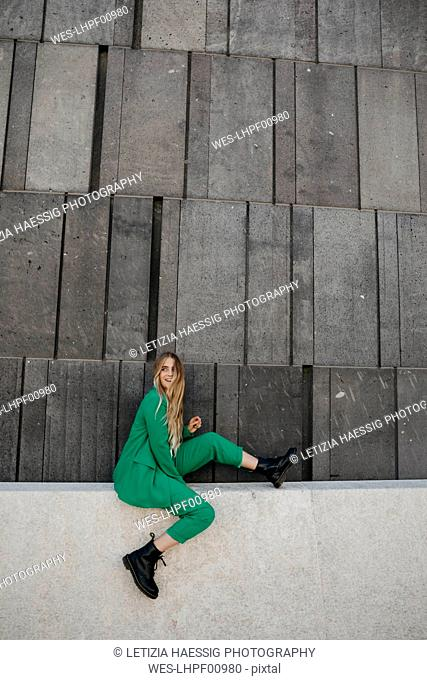 Blond young woman wearing green pantsuit sitting on a wall, Vienna, Austria