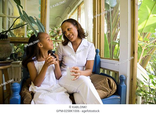 Happy African American mother and daughter sitting in indoor patio talking and bonding