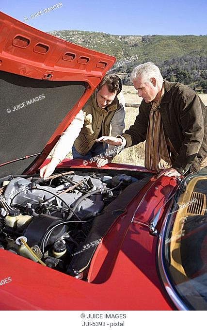 Senior man and adult son experiencing car trouble on country road, looking at engine, side view