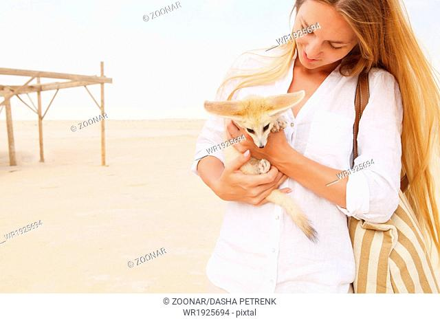 Young woman holding fennec fox